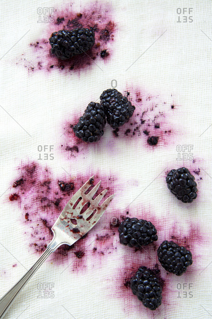 Silver fork and partially crushed blackberries on white gauze