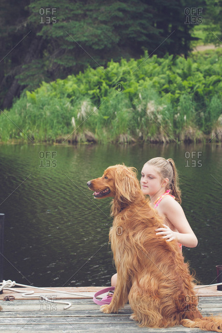 Girl petting an Irish setter dog on a pier