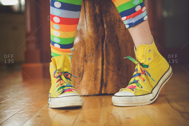Girl wearing yellow sneakers with colorful laces and tights