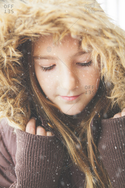Girl wearing a hooded jacket in the snowfall