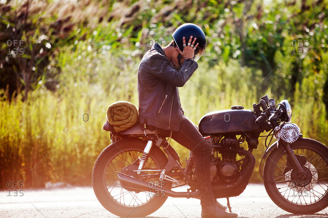 Man taking off his helmet on a motorcycle