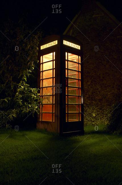 A telephone booth illuminates the dark