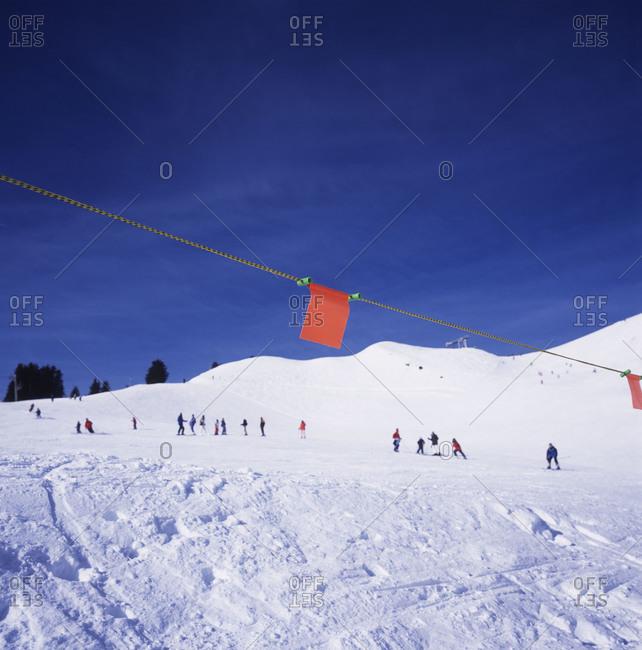 Skiers ski down a low hill