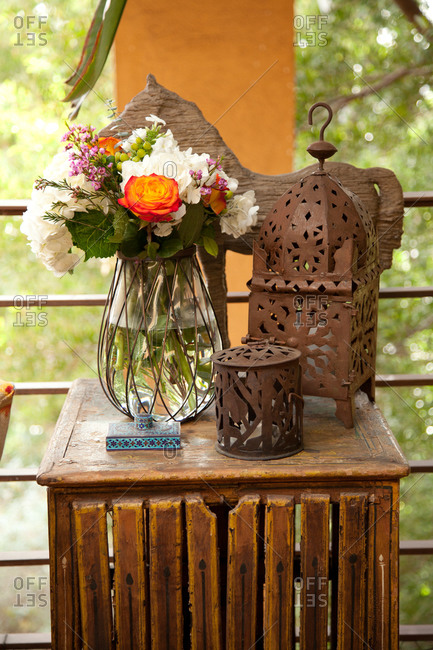 Still life of rusty hurricane lamp, a candle holder, a bouquet and a carved horse