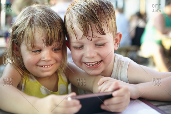 Siblings playing on smartphone