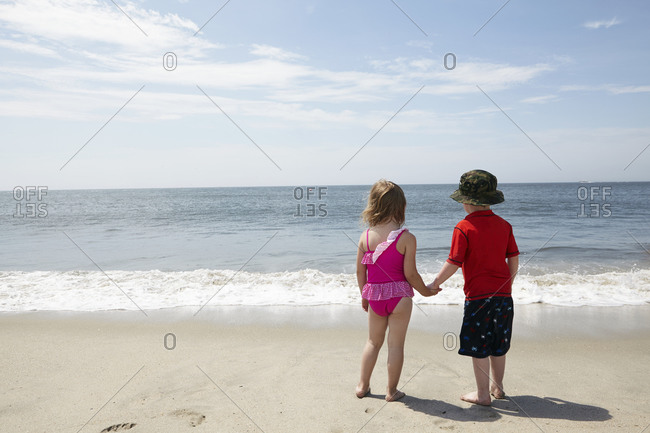 Children standing on the beach hand in hand