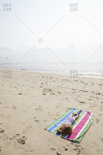 Little girl lying on a beach