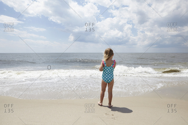 Rear view of young girl standing on sandy beach