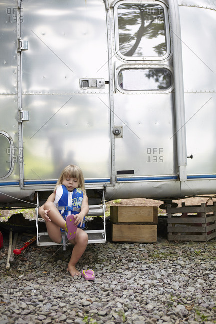 A girl sitting in front of a classic RV