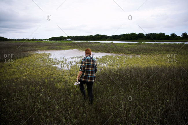 A man walks through a marsh