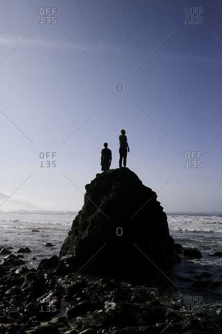 Two people stand on a rock on the shore