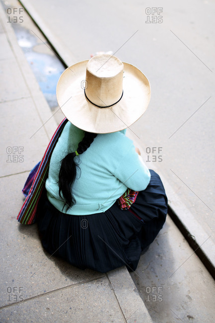 A woman sits on a sidewalk