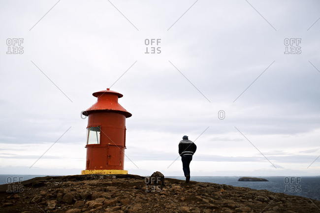 A man walking to a small red lighthouse