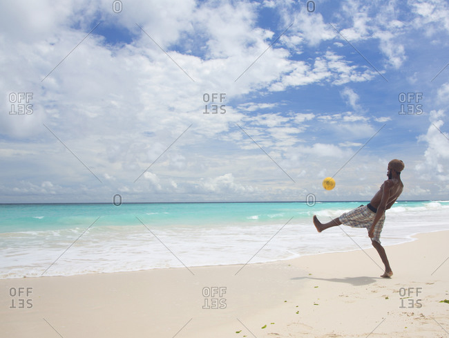 Barbados - April 28, 2013: Man playing with a soccer ball on the beach