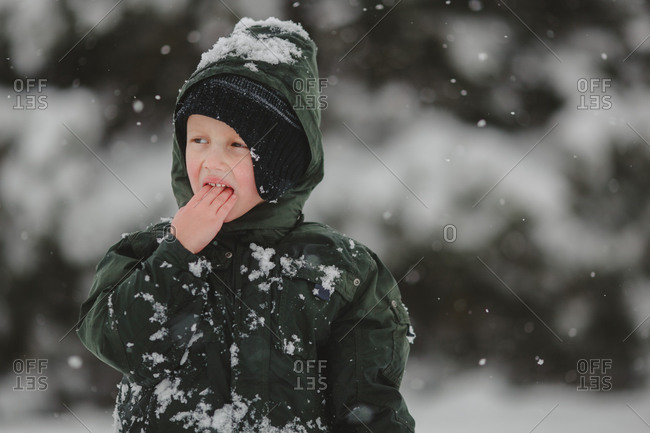 Boy in snowsuit eating snow outside