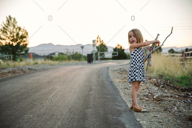 A young girl gathers sticks