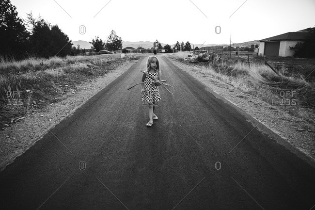 A girl walking down a road holding sticks