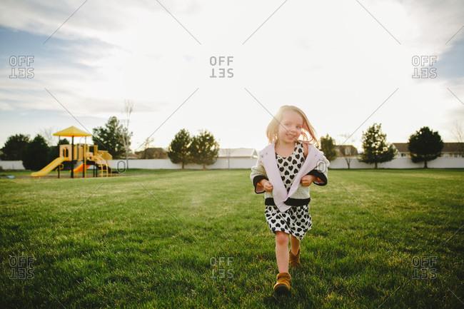 A girl walks in a suburban backyard