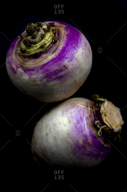 Two turnips against a black background