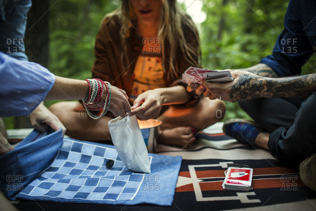 Three friends play cards outside