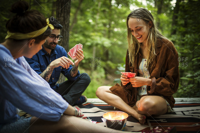 Man and two women play cards outdoors