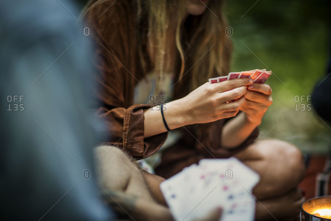 Man and friends play cards outside