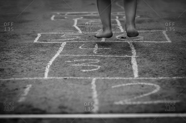 Feet of child playing hopscotch