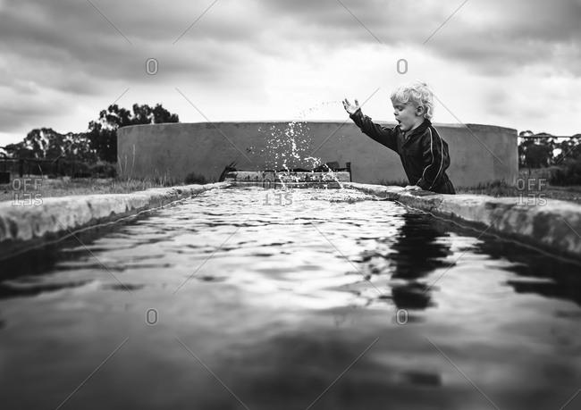 Young boy splashing water at a pool