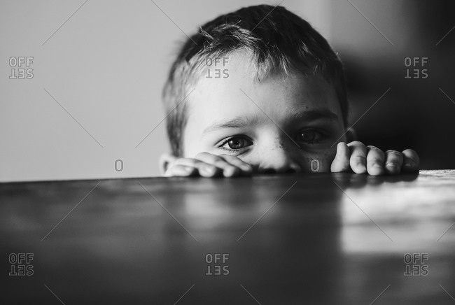 Young boy hiding behind a table