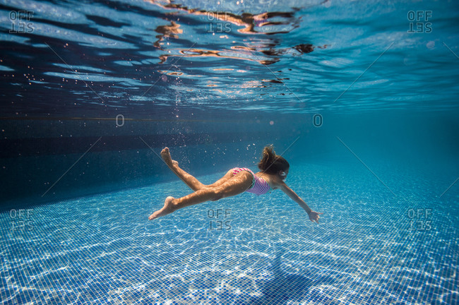 Young girl swimming underwater in a pool