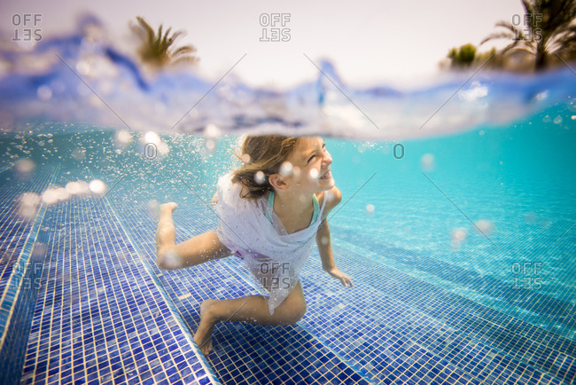 Young girl smiling underwater in a pool