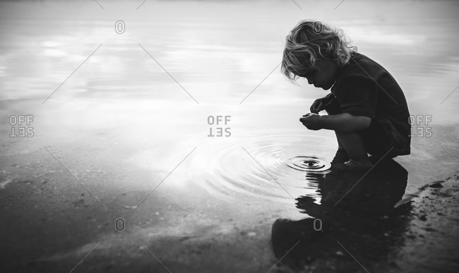 Side view of a boy crouching in puddle