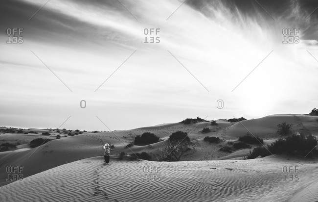 Boy running among sand dunes