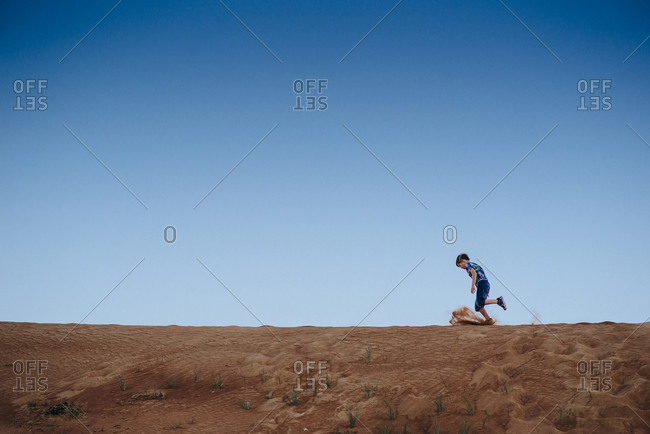 Side view of a boy running on a ridgeback of a sand dune
