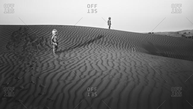 Children standing on sand dunes