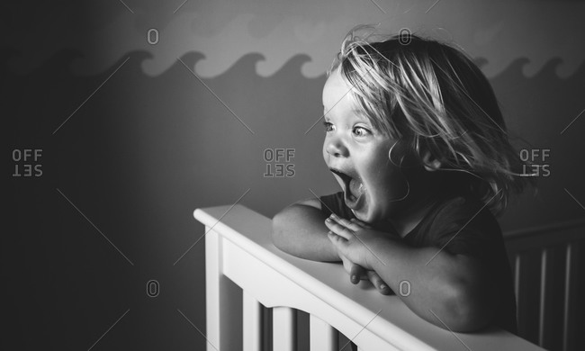 Surprised little boy in his crib
