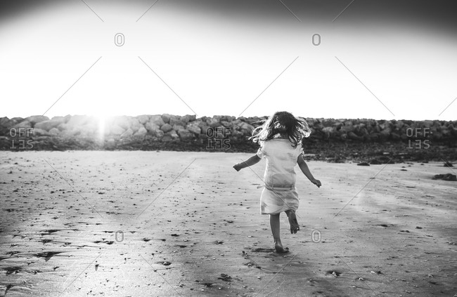 Back view of girl running on a beach