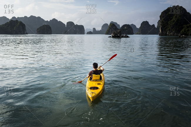Man in kayak rowing in Bai Tu Long Bay, Vietnam