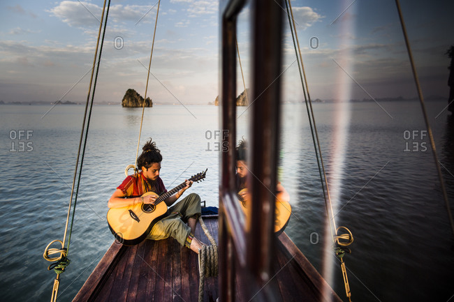 Bai Tu Long Bay, Vietnam - May 19, 2014: A young man plays an acoustic guitar on a traditional junk boat