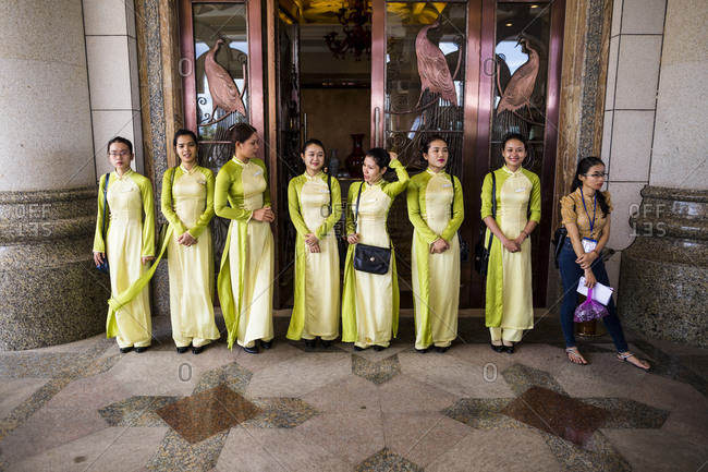 Danang, Vietnam - June 24, 2014: Vietnamese staff in ao dais see a group of Chinese tourists off from the Crowne Plaza hotel casino