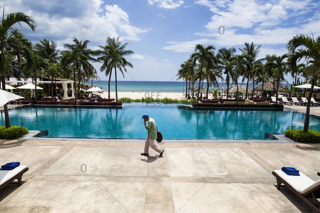 Danang, Vietnam - June 24, 2014: An employee walks past the swimming pool at the Furama Resort