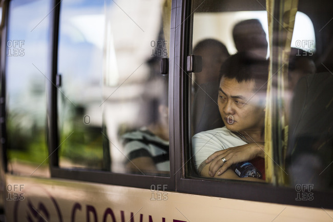 Danang, Vietnam - June 24, 2014: A Chinese tourist stares out of a tour bus window at the Crowne Plaza hotel