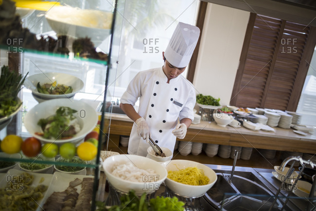 Danang, Vietnam - July 5, 2014: A chef places ingredients into a Vietnamese breakfast soup