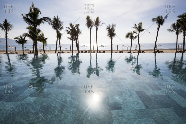 Danang, Vietnam - July 5, 2014: The sun rises over a swimming pool at a beachside resort
