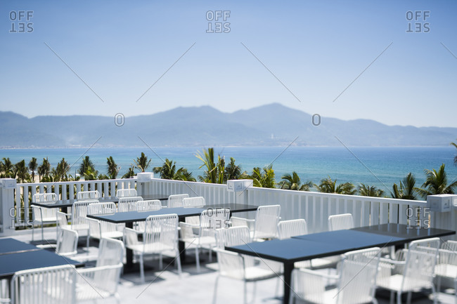 Danang, Vietnam - July 5, 2014: Outside restaurant tables overlook Son Tra Peninsula and the South China Sea