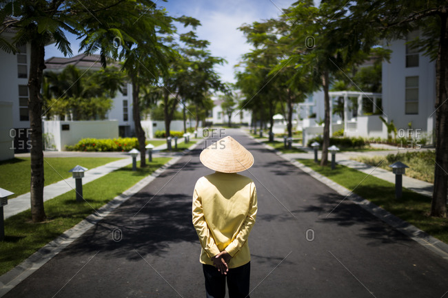 A staff member in a conical hat walks down a small street inside of a resort in Danang, along the central coast of Vietnam