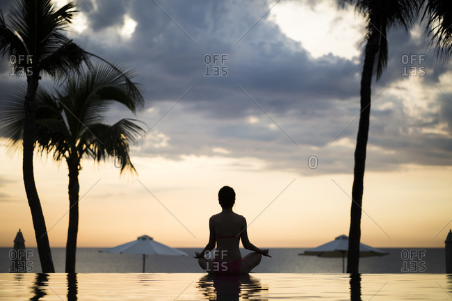 Woman doing yoga at the edge of an infinity pool