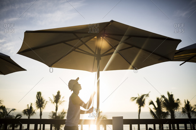 Danang, Vietnam - July 7, 2014: A staff member raises umbrellas at a restaurant on the beach as the early morning sunrises