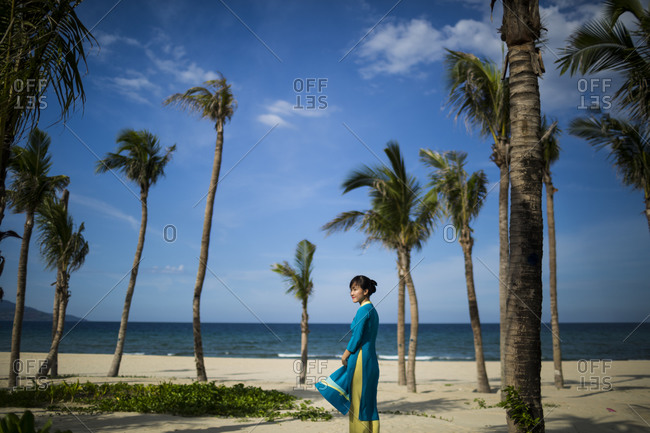Danang, Vietnam - July 6, 2014: A girl in a blue ao dai looks over her shoulder