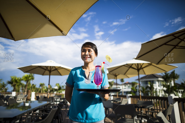 Danang, Vietnam - July 7, 2014: A waitress carries a cocktail at a beachside resort